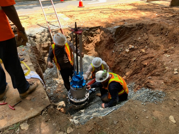 3 men in hard hats are in a hole in the road installing a valve