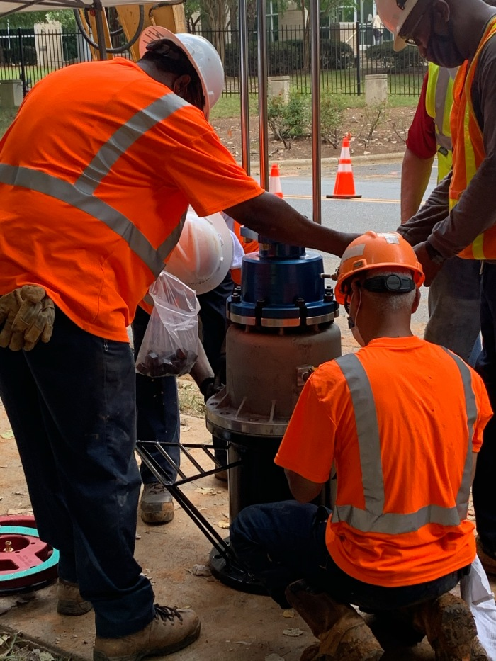 a group of men wearing hard hats and safety vests standing around a valve in the street